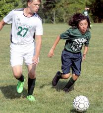 Summit Charter School's Alex Barranco, right, races for control of the ball in Sept. 12 home soccer action. The Rabun Gap player is unidentified. (Photo by Dan Brown.)