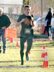 Justice Jacquot, 16, of Atlanta, crosses the finish line to win first place Thursday morning in the second annual Gobble on the Green 5K. (Photo by Don Richeson.)