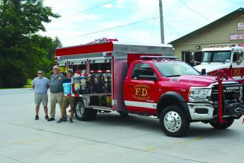 GCFD Fire Chief Randy Dillard, center, and firefighters Garrett Fowler, left, and Noah Pressler stand beside the department's newest truck at the fire station in Cashiers.