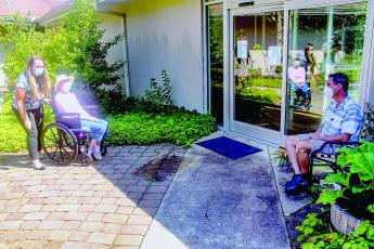 Eckerd Living Center patient, Lois Sexton, meets with her son, Jimmy during a visit in the living center's garden last week.