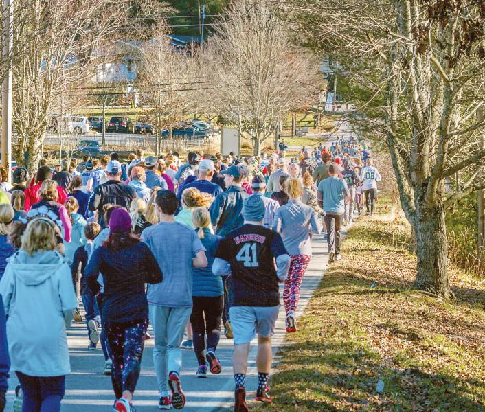 "A 500-strong mass of runners exit ""Cashiers Car Wash"" Thanksgiving morning and scamper eastward up a slight hill on Frank Allen Road as they make their way to Cashiers Lake during the 2018 Gobble on the Green 5K road race. (Photo by Irv Welling.)"
