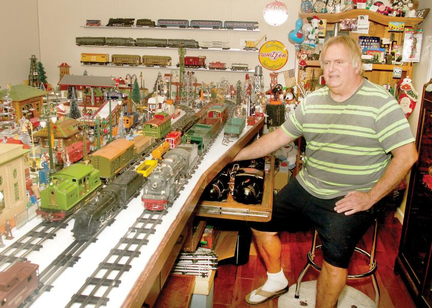 Seated amid a vast toy train display in his Norton home, Ralph Hicks shows off some of his restored vintage toy trains -- ones not unlike those he plans to give away this year in an annual Christmas gesture. (Photo by Don Richeson.)