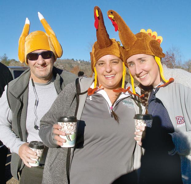 Seasonal Cashiers residents, from left, Jim Vonthron, Amanda Vonthron and Kristina Bond show off their turkey caps before the 2018 race. Many race participants wear zany costumes -- even if you aren't participating, it's entertaining to come out to the Village Green Commons Thanksgiving morning and check them out. (Photo by Don Richeson.)