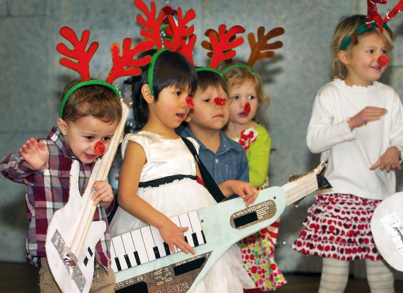 "Decked out in reindeer-theme garb, Cashiers Valley Preschool 3, 4 and 5 year olds ""play"" prop instruments and sing ""Jingle Bell Rock"" during the school's Christmas program Friday. They include, from left, Samuel Wingate, Lucy Lopez. Elias Flores-Jimenez, Leigh Helms and McKinley Pusch. (Photo by Don Richeson.)"