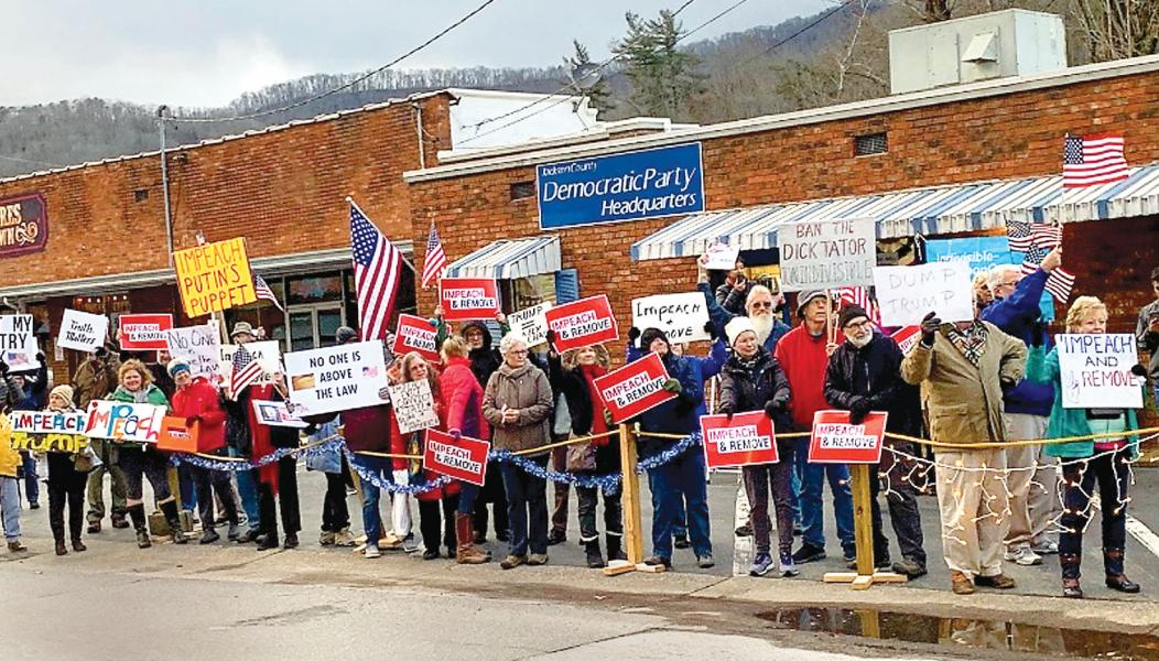 A crowd of 100 people, many waving placards, gather in front of Jackson County Democratic headquarters last week to demonstrate they favor the impeachment of President Trump.