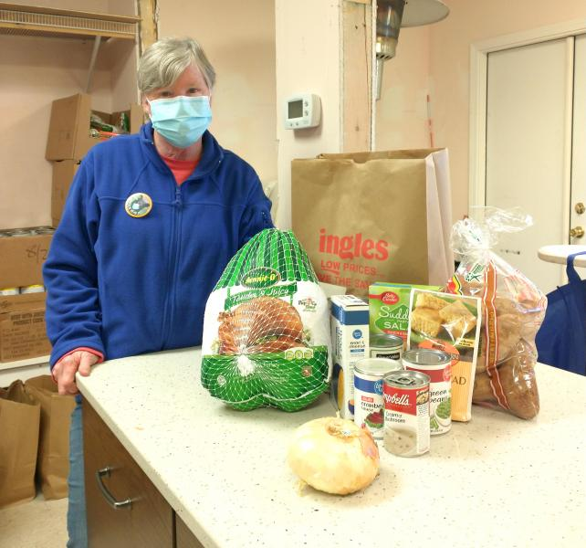Fishes and Loaves board member Susie Davis shows off the contents of this year's Thanksgiving food bags at the pantry.